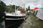 Flotte båtar i kanalen og fargerike telt frå politiske parti langs kanten