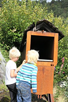 Gutane utforskar tekniske installasjonar. Her ein innretning til å dampe båtbord