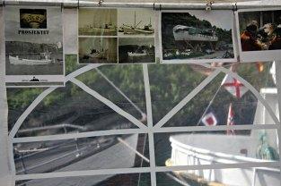 Utstilling med bilete av gamle båtar, med gamle båtar i kanalen like bak teltet