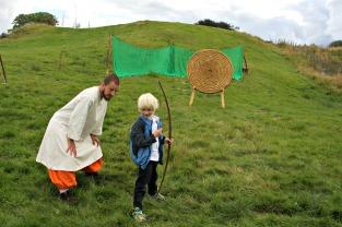Vikinglaget instruerer pil- og bogeskyting på vikingmarknad på Lygra slik at born og vaksne kan få prøve seg.