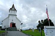 Den kvite kyrkja med det amerikanske flagget utanfor fortel av vi er komen til Amerika